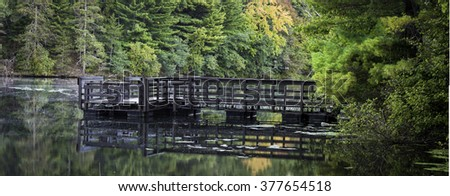 A public boat dock offers fishermen a place to tie up and unload their tackle at the end of a day on the water.  Mirror Lake State Park, Baraboo County, Wisconsin. - stock photo