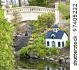 A public garden in Halifax, Nova Scotia featuring a small stream, garden bridge and a miniature model house. - stock photo