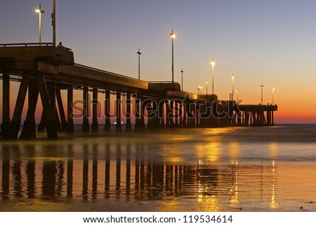 A public pier against the backdrop of a beautiful Fall sunset at Venice Beach, California. - stock photo