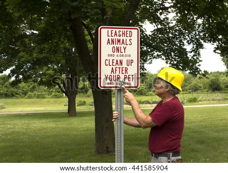 A public worker installs a sign telling people to clean up after their pets. - stock photo