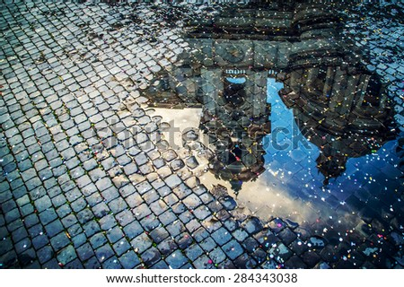 A puddle reflection of the basilica of St Agnes on Piazza Navona in Rome, Italy, covered with colorful confetti after the carnival parade - stock photo