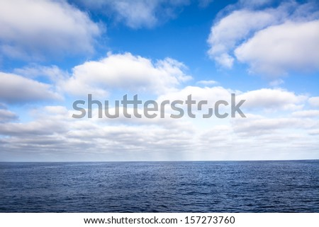 A puffy white, cloudy sky over the ocean during a bright day.