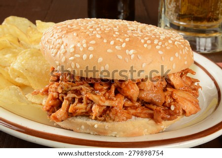 A pulled chicken sandwich on a sesame bun with chips and beer - stock photo