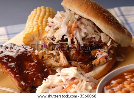 A pulled pork sandwich with cole slaw, beans and corn