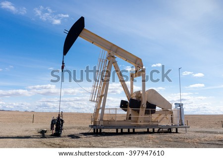 A pumpjack extracting oil out of an overground well in rural Alberta, Canada. These jacks can extract between 5 to 40 liters of crude oil and water emulsion at each stroke. - stock photo