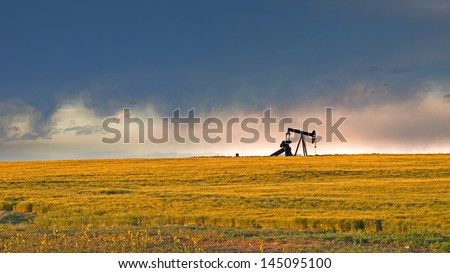 A pumpjack silhoutte with dramatic sunset. - stock photo