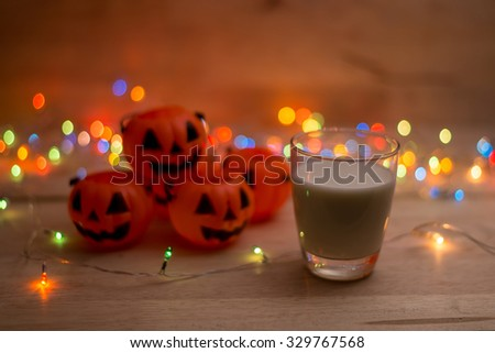 a pumpkin jack with milk and colorful blinking led bokeh lights on wood background for halloween use (selective focus technique applied)