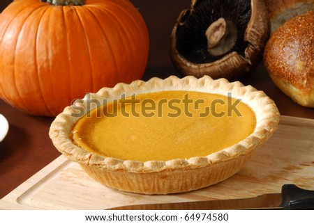 A pumpkin or sweet potato pie on a cutting board - stock photo