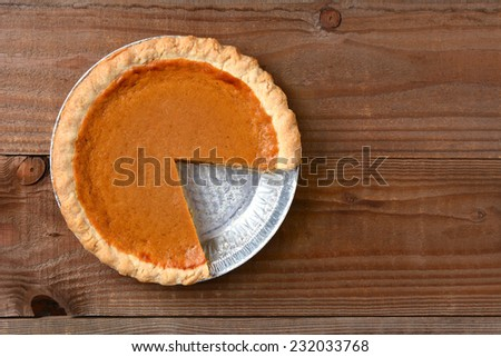 A pumpkin pie with a slice cut out. Horizontal format on a rustic wood table.  - stock photo