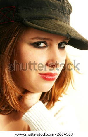 A punkish girl looks out from under her army-style cap with a faint grin. - stock photo