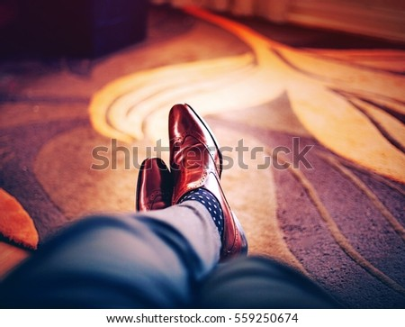 A purple filtered concept image of a man's legs in dress pants and shiny brown leather dress shoes with legs crossed sitting down under a carpet with a blurred floral design in the background.