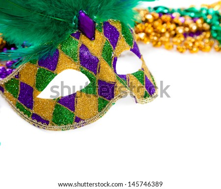 A purple, gold and green mardi gras mask and beads on white