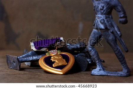 A Purple Heart Military Decoration Atop a Pile of Antique Toy Soldiers - stock photo