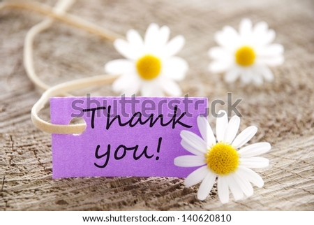 a purple label with Thank you on it and flowers in the background - stock photo