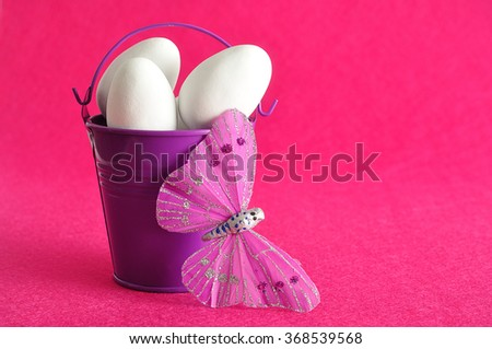 A purple metal bucket filled with white easter eggs displayed with a silk butterfly against a pink background