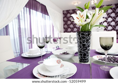 A purple styled lounge and dining room interior