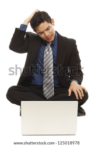 A puzzled businessman looking at his laptop