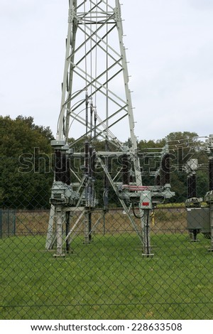 A Pylon and coils of a high voltage transformer on enclosed land / Pylon    - stock photo