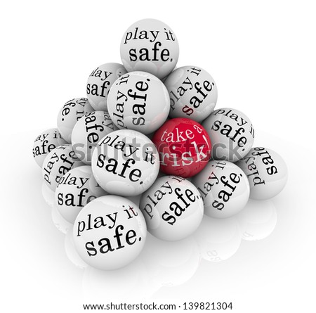 A pyramid of balls reading Play it Safe and one with the words Take a Risk to illustrate going beyond your comfort zone to rise to a challenge to grow and succeed - stock photo
