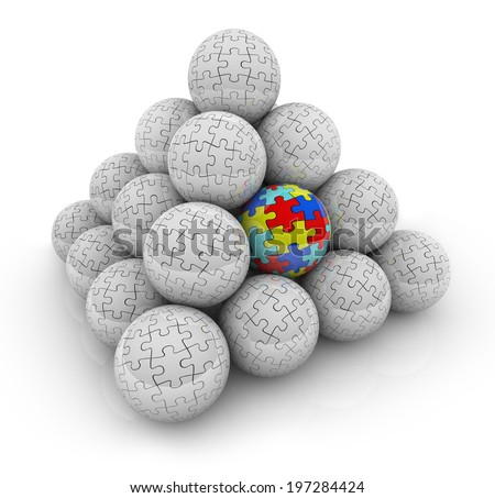 A pyramid of balls with puzzle pieces on them and one with colored pieces autism - stock photo