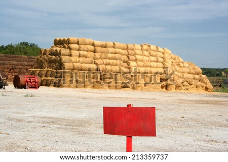 A pyramid of hay with the blue cloudy sky in the background