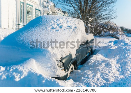 A quart ton truck buried under snow in a suburban driveway. - stock photo