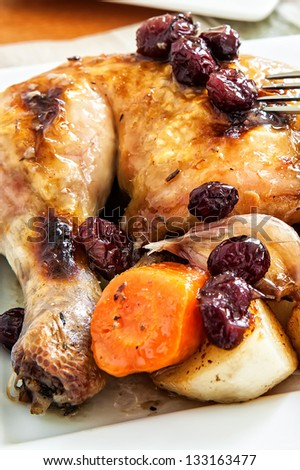 a quarter of roast chicken served with potato, carrots and cranberry.