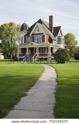A Queen Anne style Victorian house with lawn and sidewalk on a sunny afternoon