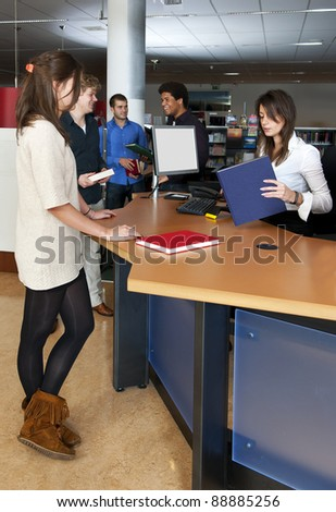 A queue of customers waiting at the check out desk, where a librarian is scanning books - stock photo