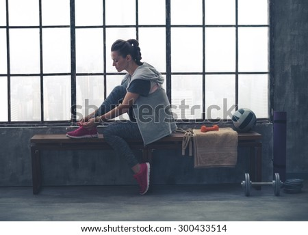 A quiet moment to tie her shoes. A fit, sporty young woman has one foot up on a bench, tying her shoelaces, as she gets ready to start her workout. - stock photo
