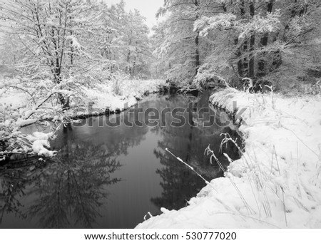 A quiet stream flows gently through a winter landscape blanketed under the first snowfall of the new season.