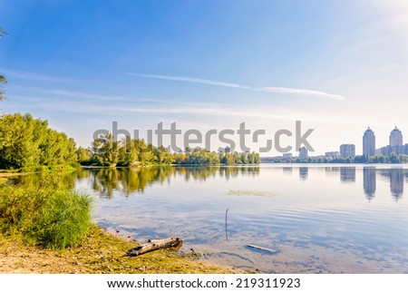 A quiet view of the river under the late summer sun, with the city skyline in the distance