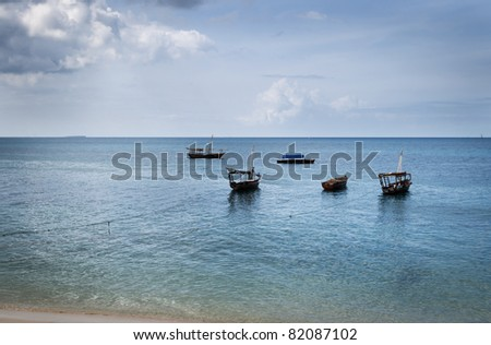 A quintet of traditional fishing wooden dhows moored off the coast of Stonetown, Zanzibar, Tanzania. - stock photo