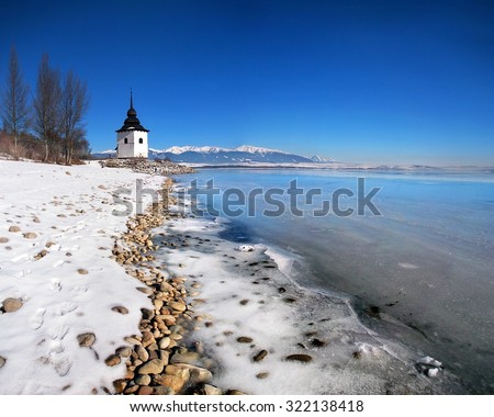 A quite rare view of showing ice-frozen waters of the Liptovska Mara lake during the cold winter. The hills of the Rohace mountains, part of Western Tatras, can be seen in the distance.