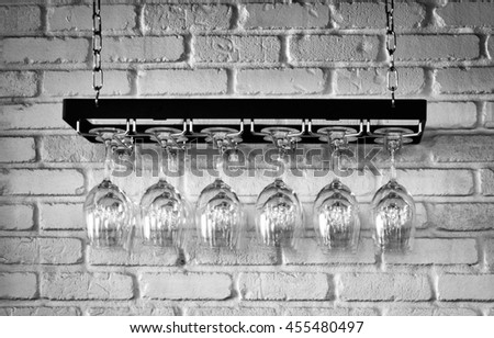 A rack of wine glasses hanging against brick wall.