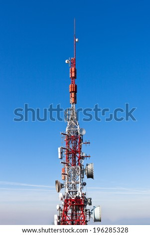 A radio communications tower with dishes against a deep blue sky