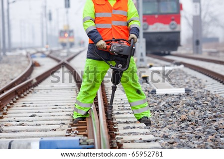 a railroad worker unscrews a screw on the rails - stock photo