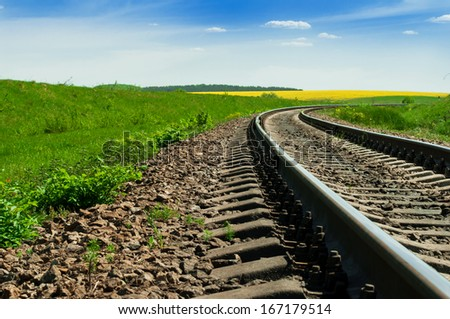 A railway turns upright through the spring green field. The sky is brightly blue with some white clouds - stock photo