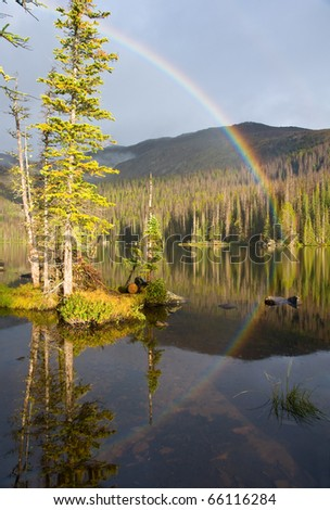 A Rainbow is reflected on the calm waters of a wilderness lake - stock photo