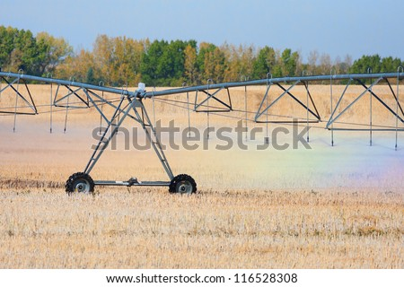 A rainbow of colors are reflected in the water droplets coming from an agricultural watering system pivot. - stock photo