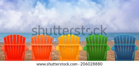 A rainbow of colors of wooden beach chairs are lined up along the water shore. There is copyspace in the clouds for a vacation message. - stock photo