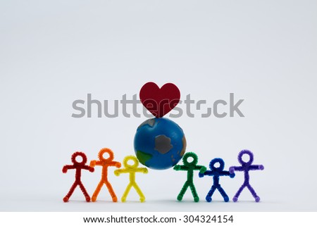 A rainbow of pipe cleaner people holding the world with a heart. Working in unity to love and save the world. This photo could be used for multicultural, international, educational, or other ideas. - stock photo
