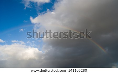 A rainbow over a dark sky after the storm. - stock photo
