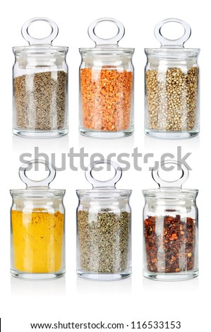 A range of six transparent glass jars of different spices and herbs