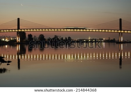 A rapid transit commuter train, crosses the Fraser River from Richmond into Vancouver. The train is a streak of light crossing the bridge due to the long exposure. British Columbia, Canada.
