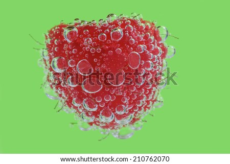 A Raspberry in Clear Fizzy Water Against a Green Background. - stock photo