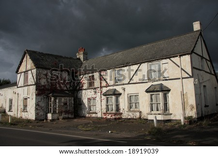A rather dramatic image of an abandoned roadside hotel in Devon England. Hotel crumbling into disrepair caught in a moment of bright sunshine on an otherwise dark and stormy day