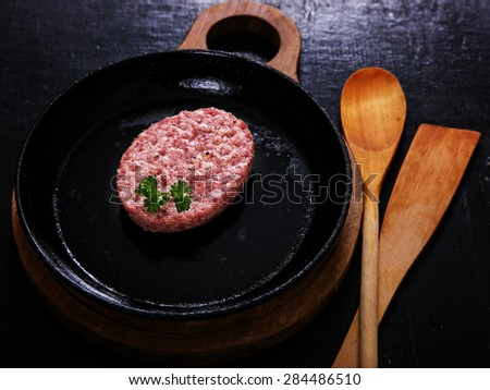 A raw cutlet on a cast iron skillet before frying - stock photo