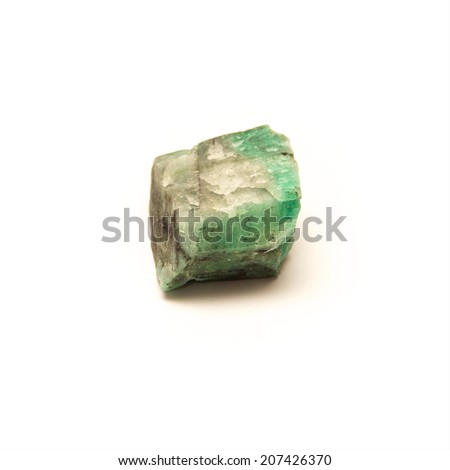 A raw uncut piece of emerald shot over white.