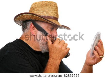 a Real Cowboy shaves with a large knife. isolated on white with room for your text - stock photo